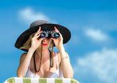 Beautiful young woman in bikini looking through binoculars at the tropical beach — Foto de Stock