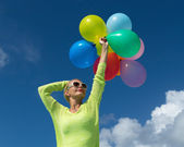 Woman holding balloons against cloud and sky — Stock fotografie