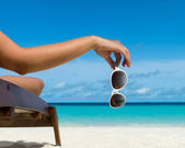 Young girl lying on a beach lounger with glasses in hand on the tropical island — Foto Stock
