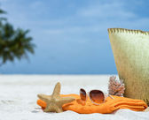 Summer beach bag with starfish,towel,sunglasses and flip flops on sandy beach — Stock Photo