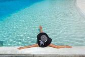 Mujer con sombrero relajante en la piscina — Foto de Stock