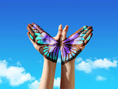 Strony i motyl ręczne, malowanie, tatuaż, nad niebieski niebo — Zdjęcie stockowe