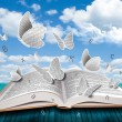 Open book with butterflies letters on blue sky  — Stock Photo