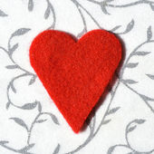 Red felt heart on decorative background — Zdjęcie stockowe