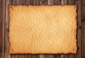 Old wrinkly paper on brown aged wood. Old paper sheet. Digital — Stock Photo