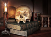 Vintage skull on antique book with candle and hourglass — Stock Photo