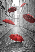 Red umbrellas flying on the street. Conceptual image — Stock Photo