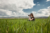 Beautiful elegant woman standing on a green meadow — Stock Photo