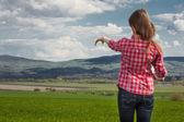Beautiful elegant woman standing on a green meadow — ストック写真