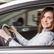 Join me for a drive. Attractive young woman sitting at the front seat of the car looking at camera — Stock Photo #45711569