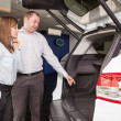 This car is exactly what we want. Beautiful young couple standing at the car dealership and making their decision — Stock Photo #45711629