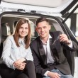 Happy young couple sitting at back of car — Stock Photo #45711631