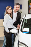 This car is exactly what we want. Beautiful young couple standing at the car dealership and making their decision — Stock Photo