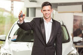 Great choise! Handsome young classic car salesman standing at the dealership holding a key — Stock fotografie