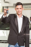 Great choise! Handsome young classic car salesman standing at the dealership holding a key — Stock Photo