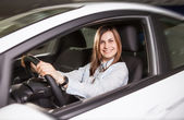 Join me for a drive. Attractive young woman sitting at the front seat of the car looking at camera — Foto de Stock