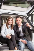 Happy young couple sitting at back of car — Stockfoto
