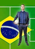 Businessman with soccer ball on a brazil flag — Stockfoto