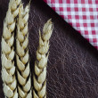 Wheat and check napkin on leather — Stock Photo