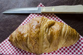 Croissant and knife on a gingham nankin — Stock Photo