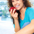 Beautiful happy female eating an apple — Stock Photo #29919029