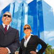 Business mand womstanding in front of building — Stock Photo #29919147