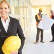 Happy confident business woman holding hardhat giving thumbs up — Stock Photo