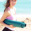 Beautiful young white female holding yoga mat — Stockfoto
