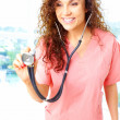 Close-up of a friendly beautiful nurse holding stetescope — Stock Photo #29919561