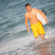 Hispanic male with surfboard at the beach running — Stock Photo #29919585