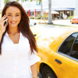 Businesswoman hailing a yellow taxi cab — Stock Photo