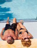Volwassen caucasion mannelijke en vrouwelijke ontspannen in het zwembad. — Stockfoto