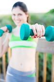 Happy beautiful hispanic female weight training on the boardwal — Stock Photo