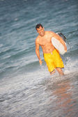 Hispanic male with surfboard at the beach running — Stock Photo