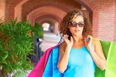 Schöne Frau mit Einkaufstüten mit Sonnenbrille — Stockfoto