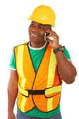 Happy african american construction worker on cellphone — Stock Photo