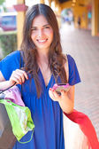 Beautiful young latin girl text messaging with shopping bags — Stock Photo