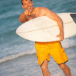 Hispanic male with surfboard at the beach pointing — Stock Photo #29920111