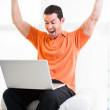 Stock Photo: Happy work at home male working on laptop smiling