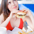 Beautiful young latin girl eating hamburger — Stock Photo