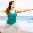 Beautiful female doing yoga warrior pose — Stock Photo