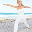 Beautiful woman doing yoga on the beach in warrior pose — Stock Photo