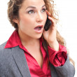 Beautiful business woman talking on cellphone in shock — Stock Photo