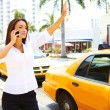 Businesswomhailing yellow taxi cab — Stock Photo #29920621