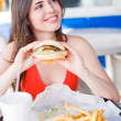 Beautiful happy young latin girl eating hamburger — Stock Photo