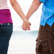 Young happy couple holding hands on beach — Stock Photo