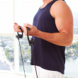 Caucasian male doing resistance training indoors — Stockfoto
