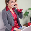 Stock Photo: Beautiful business woman holding laptop talking on cellphone