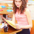 Attractive young woman reading menu — Stock Photo