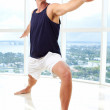 Stock Photo: Caucasian male doing yoga warrior pose